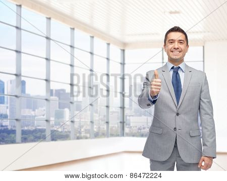 business, people, gesture, real estate and success concept - happy smiling businessman in suit showing thumbs up over city office window background