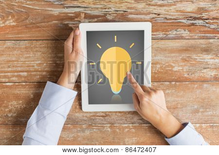 business, education, inspiration, people and technology concept - close up of hands with lighting bulb icon on tablet pc computer screen and coffee cup at table