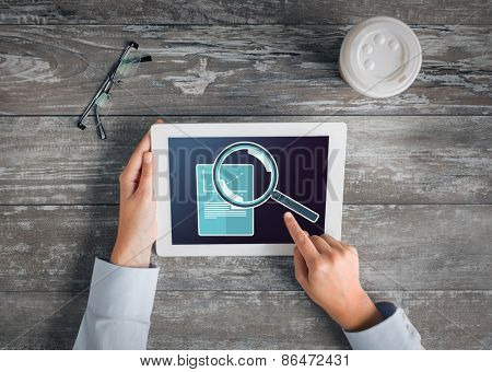 business, people, statistics and technology concept - close up of hands pointing finger to tablet pc computer screen showing magnifier and graph on table