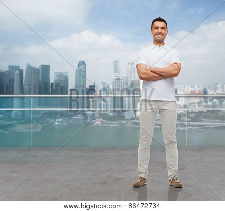 business, travel, tourism and people concept - smiling man with crossed arms over city background