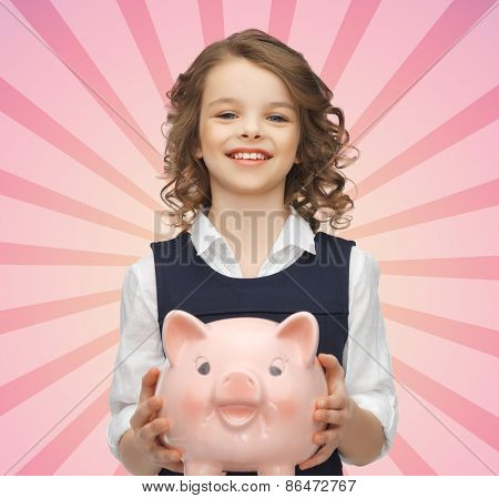 people, money, finances and savings concept - happy girl holding piggy bank over pink burst rays background