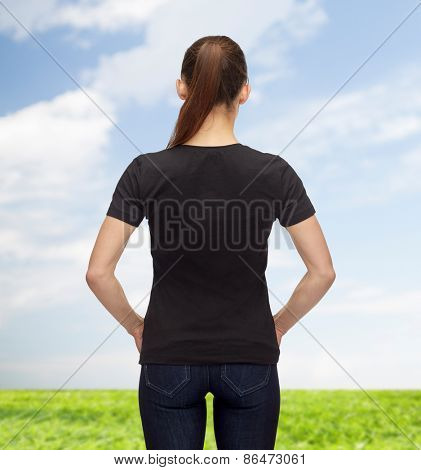 t-shirt design, advertisement and people concept - woman in blank black t-shirt from back over blue sky and grass background