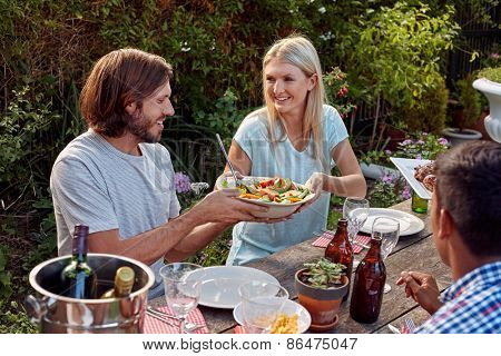 woman passing fresh healthy salad at outdoor friends dinner party gathering