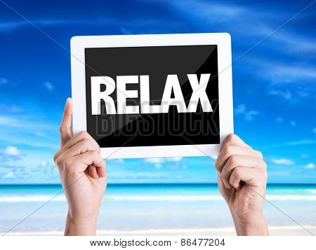 Tablet pc with text Relax with beach background