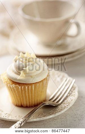 Closeup of vanilla cupcake with tea cup in background