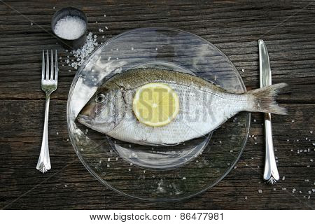 Raw fish on plate with knife and fork