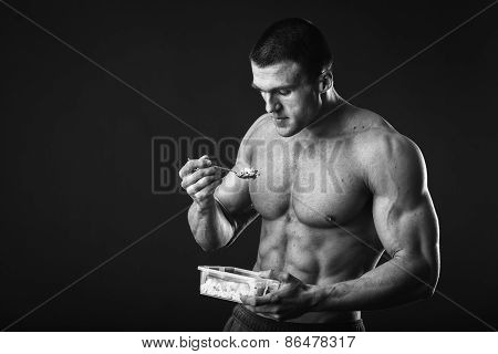Strong, healthy man posing on a black background.