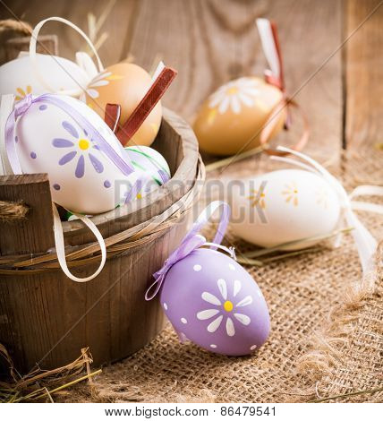 Colorful easter eggs in a basket on a wooden background