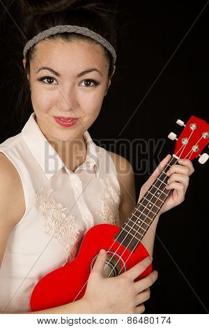 Teen Asian American Girl Playing A Red Ukulele