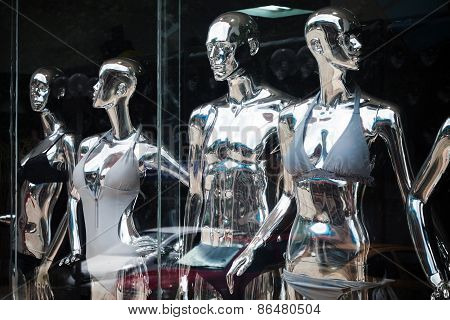 Shining Metallic Mannequins Standing In A Window