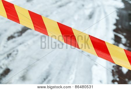 Red And Yellow Striped Tape On Winter Road