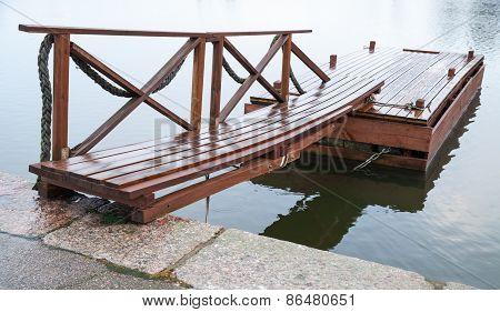 Shining Wet Wooden Floating Pier In Still Lake Water