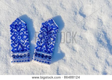 Blue Handmade Mittens In The Snow On A Sunny Day