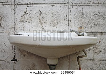 Old White Washbasin On Dirty Wall