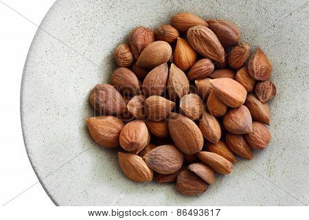 Apricot kernels on a round plate isolated