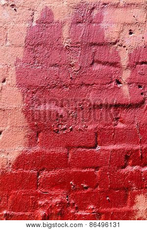 A red textured brick wall that has a painted red stain