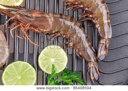 Raw shrimps on pan with lemon.