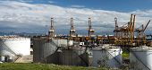 stock photo of fuel tanker  - Oil tanks in the port with loading kranes and tankers on the background - JPG