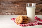 stock photo of milk glass  - Tasty cookies and glass of milk on rustic wooden background - JPG