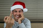 foto of middle finger  - young man wearing a santa hat with his middle finger up for a bad santa concept - JPG
