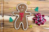 image of gingerbread man  - holiday classic a gingerbread man cookie on a wooden table - JPG