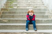 image of pullovers  - Adorable little boy with blond hair sitting on steps in a city on a nice sunny day - JPG