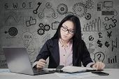 picture of writing  - Portrait of young businesswoman working with laptop while writes on planner book - JPG