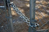 stock photo of gate  - Close up shot of a strong chain and lock securing a gate to a chain link fence - JPG