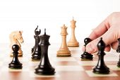 pic of chess piece  - Playing chess - a hand moving chess pieces on a chessboard