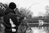 stock photo of fishermen  - Young fisherman catches winter spinning - JPG
