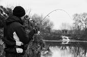 picture of fishermen  - Young fisherman catches winter spinning - JPG