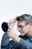 pic of dandruff  - Guy checking out his hair with a mirror - JPG