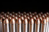 stock photo of cartridge  - Loaded cartridges with bullets that have a red tip on black  - JPG
