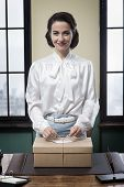 stock photo of secretary  - Smiling vintage secretary holding a mail package with rope and label - JPG