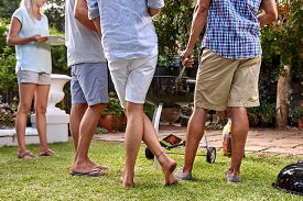 stock photo of gathering  - friends outdoors at garden barbecue party gathering - JPG