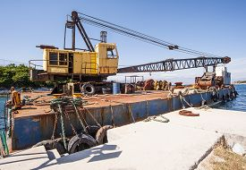 stock photo of dredge  - An industrial crane mounted onto a boat for dredging operations - JPG