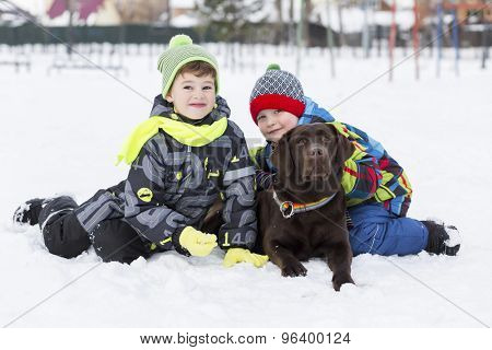 Kids of school age with dog in winter park
