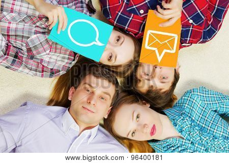 Group of young smiling people lying on floor in circle with phone symbols