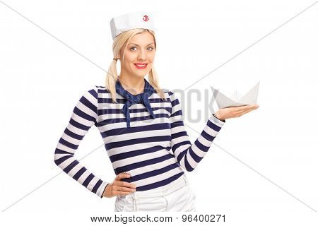 Young female sailor holding a small paper boat and looking at the camera isolated on white background