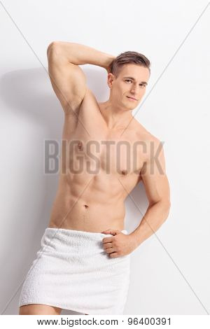 Vertical shot of a handsome young man posing with a white bath towel around his waist and looking at the camera