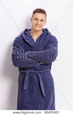 Vertical shot of a confident young man in a blue bathrobe posing in front of a white wall