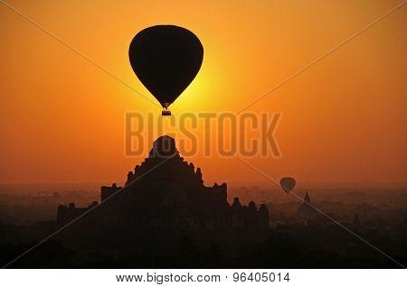 Hot air balloon over temple at sunrise, Bagan, Burma