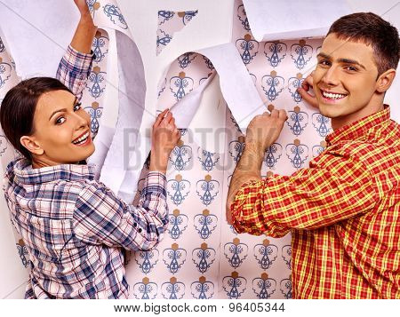 Happy family man and woman glues wallpaper at home.