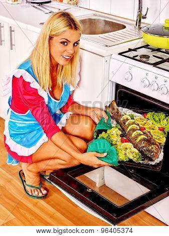 Happy woman prepare fish grill  in oven.