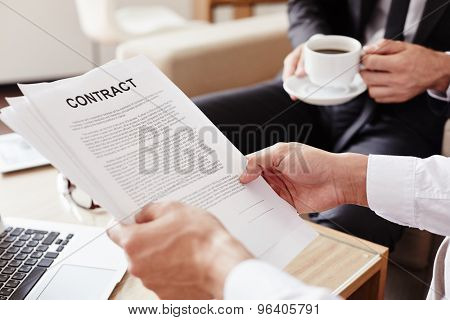 Male employee holding contract and reading it