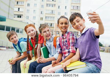 Modern school learners making selfie outside