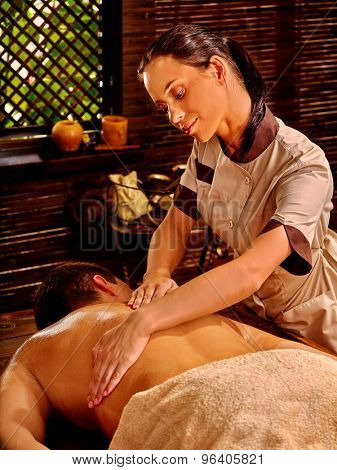 Man  having oil Ayurveda spa treatment with window.