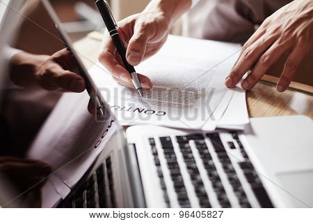 Hand of employee with pen before signing contract