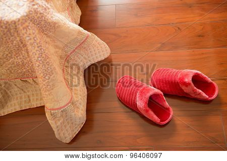 Pair Of White Slippers On Floor Nearby A Bed