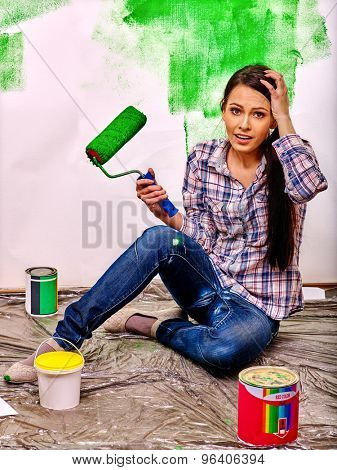 Happy woman sitting on floor  paint wall at home.